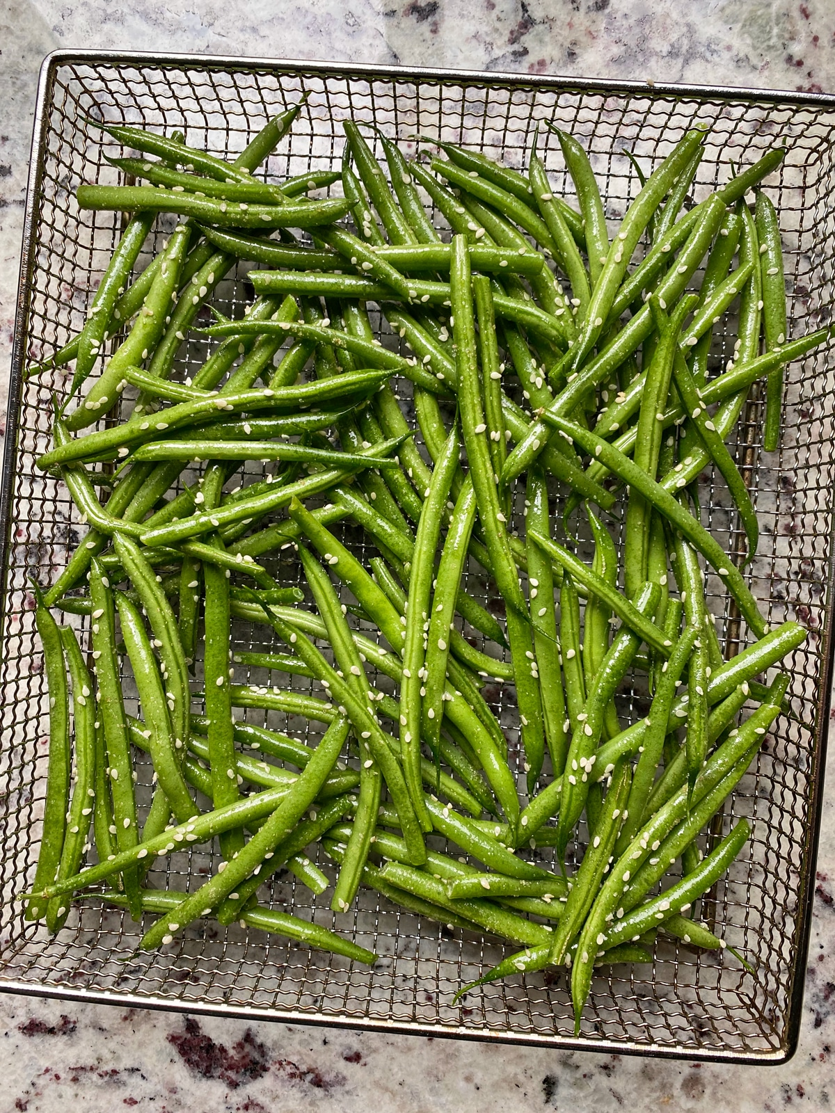 uncooked green beans in air fryer basket