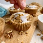 sprinkling bee pollen on iced muffins